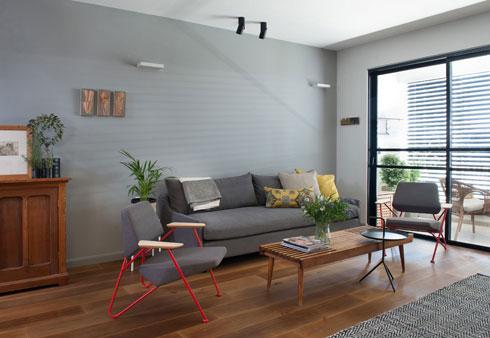 הקיר שעליו נשענת הספה נצבע באפור כהה, ואילו שאר הקירות נצבעו באפור בהיר (צילום: גלית דויטש)