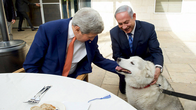 One is preaching, the other is biting. Netanyahu and Kerry with the prime minister's dog (Photo: Reuters)