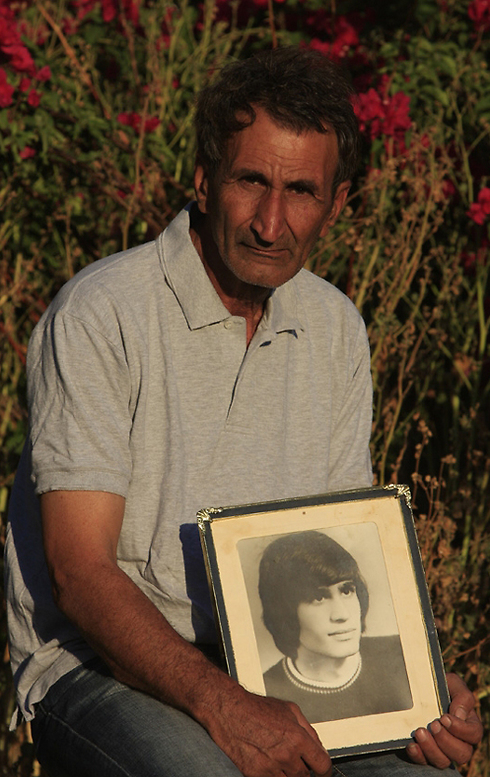 Haim Shahar and a photo of his brother, Eliyahu Shahar, who was murdered in the 1979 terror attack (Photo: Tsafrir Abayov)