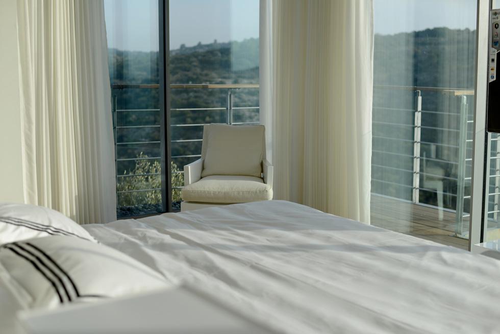 חדר השינה המרכזי, כמו בסלון בקומה שמתחתיו, פונה אל הנוף ללא כל חסימה, למעט מסך זכוכית דק (כשרוצים חושך מורידים את הוילונות החשמליים והאטומים)