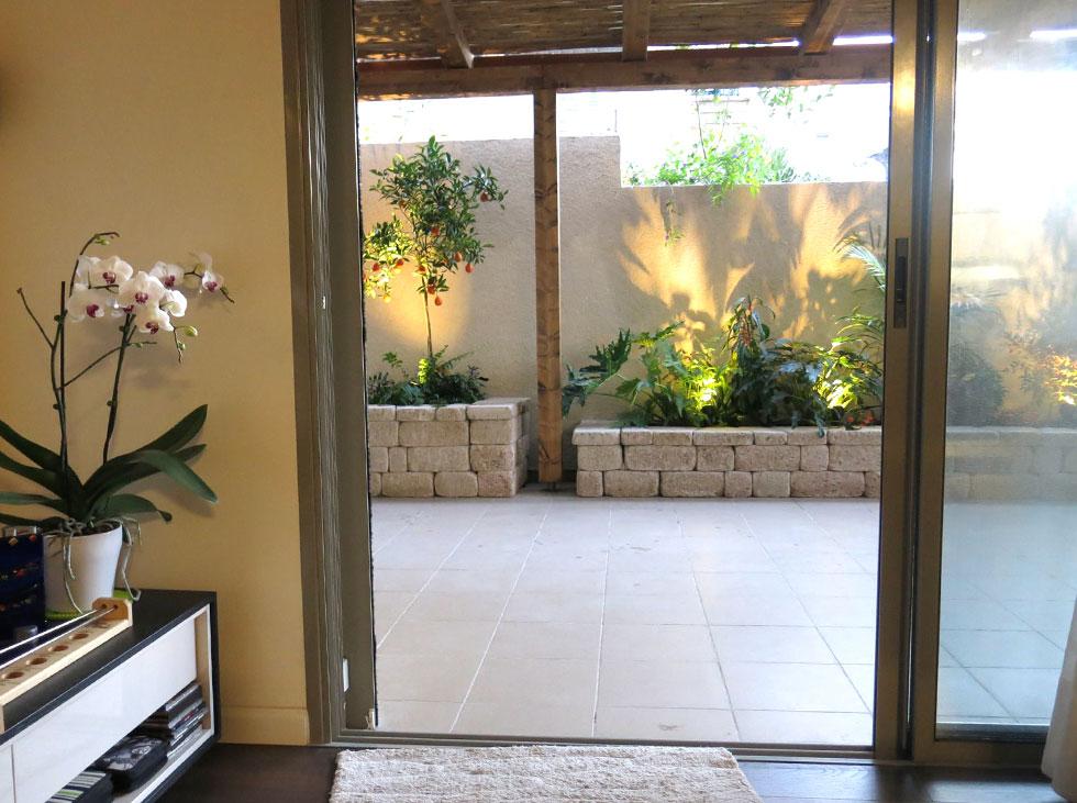 מבט מתוך הדירה אל גינת המרפסת הבנויה מאבן מתועשת כורכרית. גופי תאורה סמויים מדגישים את הצמחייה הטרופית (צילום: באדיבות רודה גינון גגות)