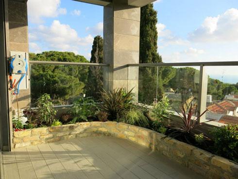 המרפסת בסיום השתילה: הערוגה בנויה מבריק limestone המיובא מאירופה. בפינה השמאלית מערכת השקיה מקצועית ומיכל לדישון אוטומטי (צילום: באדיבות רודה גינון גגות)