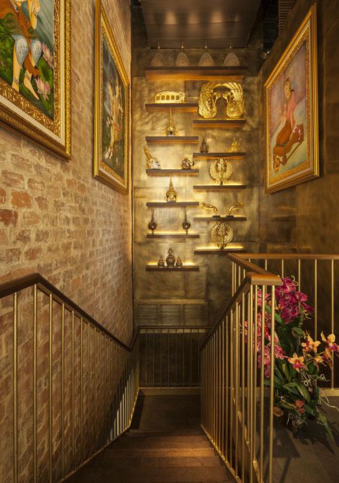 לפסלונים על מדפי גרם המדרגות שיורד לבר התחתון ולשירותים יש משמעויות בתרבות תאילנד (צילום: עמית גרון)