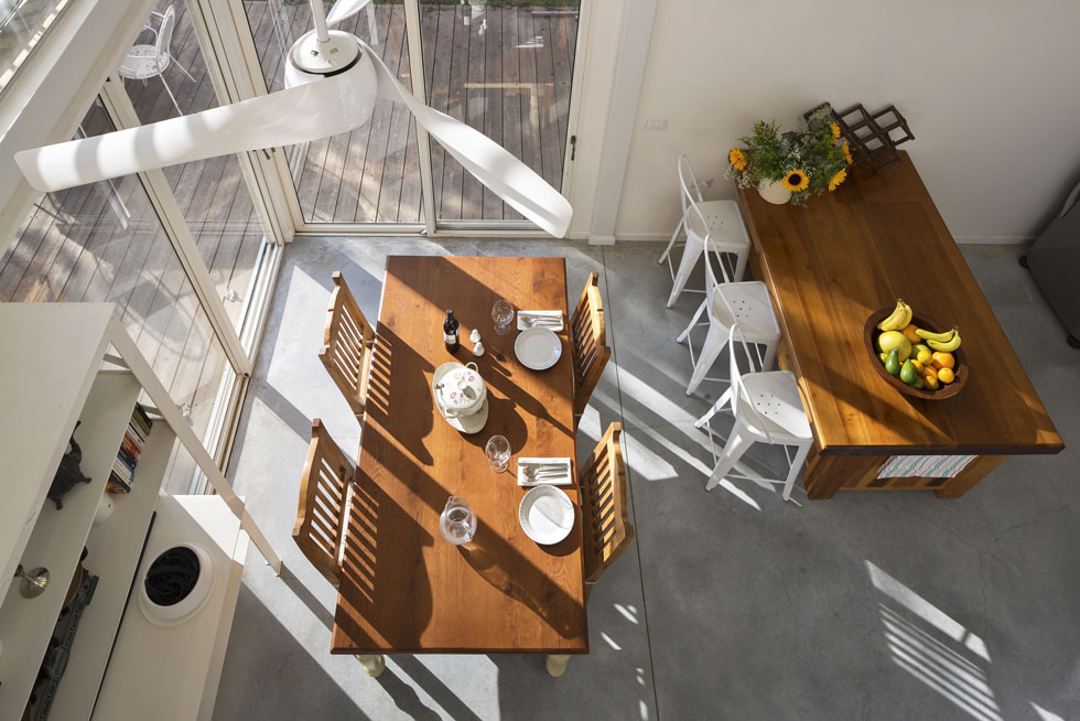 מבט על המטבח מהגשר בקומה העליונה. רצפת בטון מוחלק, חלונות אלומיניום לבנים ותריסים חיצוניים נאספים משלימים את המראה המתועש (צילום: שי אפשטיין)