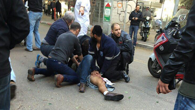 Volunteers and passersby attending to the wounded following a shooting attack in central Tel Aviv