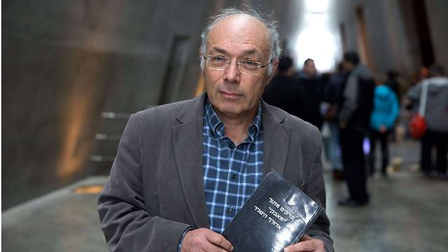 Israeli Dan Michman, head of the Yad Vashem International Institute for Holocaust Research, holds a copy of the Hebrew version of 'Mein Kampf' book during an interview at the Yad Vashem Holocaust Museum in Jerusalem (Photo: AFP)