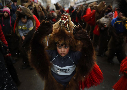 בעיר קומנשט שברומניה ערכו מצעד לגירוש הרוחות הרעות של השנה החולפת. משתתפי המצעד לבשו עורות דובים בשל האמונה הקדומה שדובים הם חיות קדושות (צילום: AFP) (צילום: AFP)