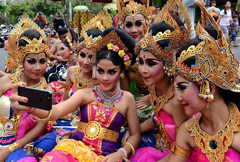 נערות בעיר דנפסאר שבאינדונזיה בתמונת סלפי במהלך החגיגות לרגל כניסת שנת 2016 (צילום: AFP) (צילום: AFP)