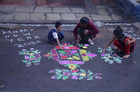"""נשים הודיות מציירות בחול צבעוני בשעת בוקר מוקדמת מחוץ לבתים בעיר היידראבאד בטכניקה הינדית מיוחדת הנקראת """"ראנגולי"""". בדרך זו הן מברכות את בני המשפחה והחברים לרגל השנה החדשה (צילום: AFP) (צילום: AFP)"""
