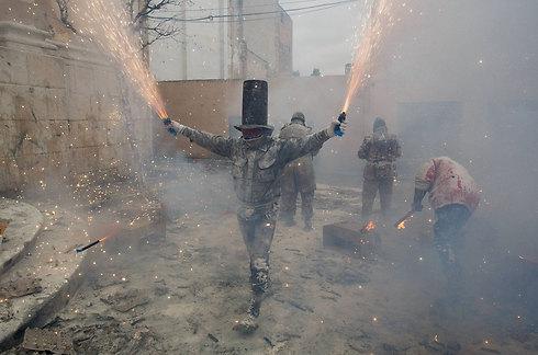 """בעיר איבי שבספרד חגגו את פסטיבל הקמח בקרב קמח שמלווה בהשלכת ביצים וחזיזים. בצד אחד של המתרס ניצבת קבוצה של גברים נשואים ש""""כובשת"""" את העיר וכופה על התושבים חוקים מגוחכים. בצד השני ניצבת קבוצת גברים אחרת שמנסה להשתלט מחדש על העיר (צילום: gettyimages) (צילום: gettyimages)"""