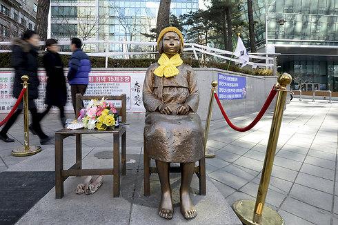 """פסל ילדה מול שגרירות יפן בסיאול שמסמל את אלפי הנשים, בהן דרום קוריאניות, שאולצו על ידי צבא יפן לשמש כשפחות מין במהלך מלחמת העולם השנייה. ראש ממשלת יפן שינזו אבה הביע התנצלות היסטורית בפני דרום קוריאה על הטיפול של ארצו ב""""נשות הניחומים"""" וארצו תשלם פיצויים לקורבנות שנותרו בחיים (צילום: רויטרס) (צילום: רויטרס)"""