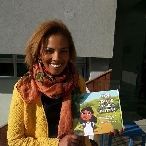 ווביט וורקו-מנגסטו עם ספר הילדים שכתבה ()