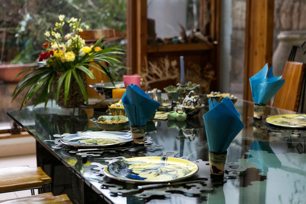 את הפלייסמנט, הצלחות וכלי ההגשה המעטרים את השולחן עיצבה בעלת הבית, ואת הצלחות מעטרים ציורים פנטסטיים של דינוזאורים, עמודים קלאסיים וצמחייה כחולה (צילום שירן כרמל)