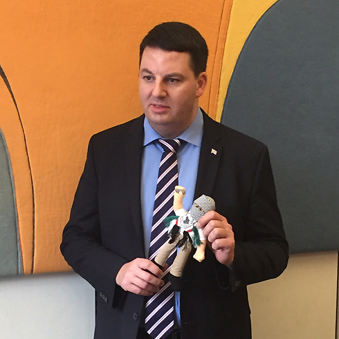 """British MP Andrew Percy holding an """"incitement doll"""""""