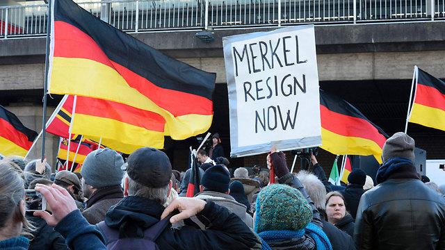 """הפגנה נגד האיסלאם בקלן, גרמניה. """"מרקל תתפטרי"""" (צילום: AP)"""