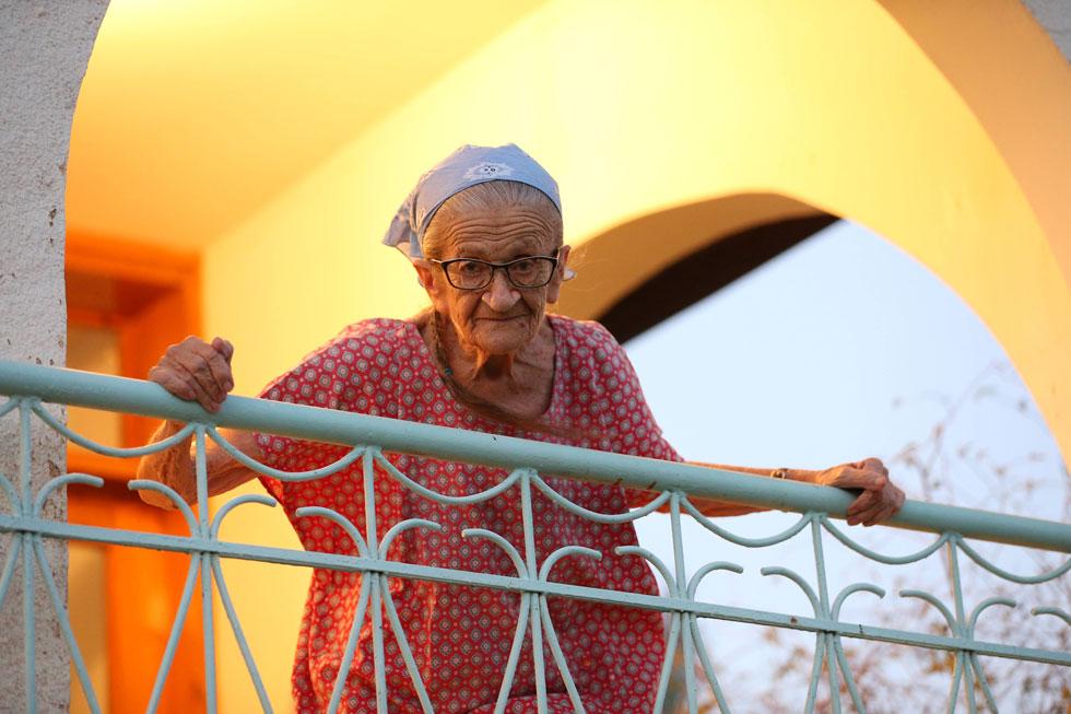 נעמי פולני בביתה שבמושבה כינרת. היא לא מדברת עברית - היא מדברת נעמי-פולנית, שזאת עברית משודרגת, עברית שאתה יכול לא רק לשמוע, אלא ממש להרגיש, למשש, לטעום ולהריח. עברית שמפעילה את כל החושים (צילום: אלעד גרשגורן)