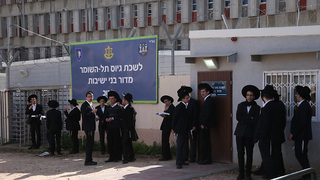 Haredim outside an army induction center (Photo: Motti Kimchi)