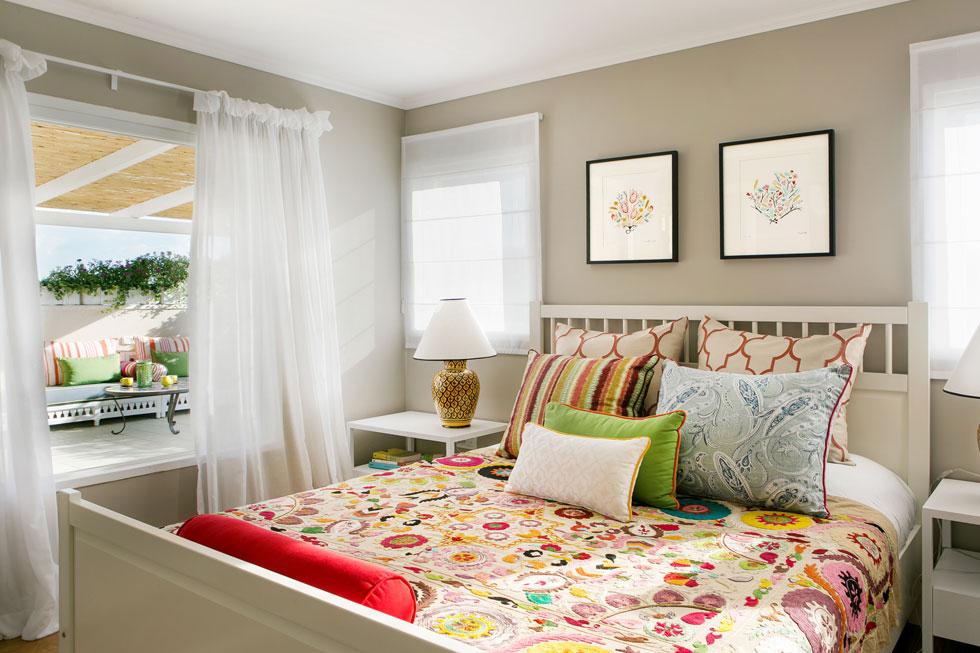 חדר ההורים בקומת הגג אינו גדול (25 מ''ר כולל חדר רחצה) - אך הוא נפתח למרפסת רחבת ידיים. המיטה סטנדרטית, אך הכיסוי שעליה, יחד עם רהיטי החוץ, מכניסים צבע ועניין גם לכאן (צילום: שירן כרמל)