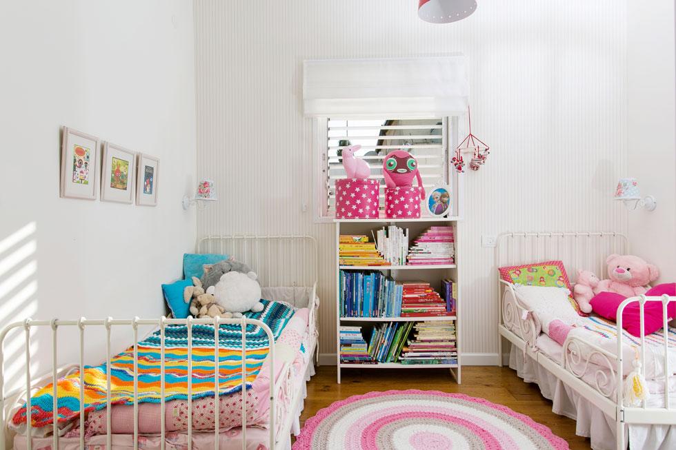 בשני החדרים של הבנות – חדר השינה (בתמונה) וחדר המשחקים – הודגש אחד הקירות באמצעות טפט, והוא משמש כעוגן לפריטים השונים (צילום: שירן כרמל)