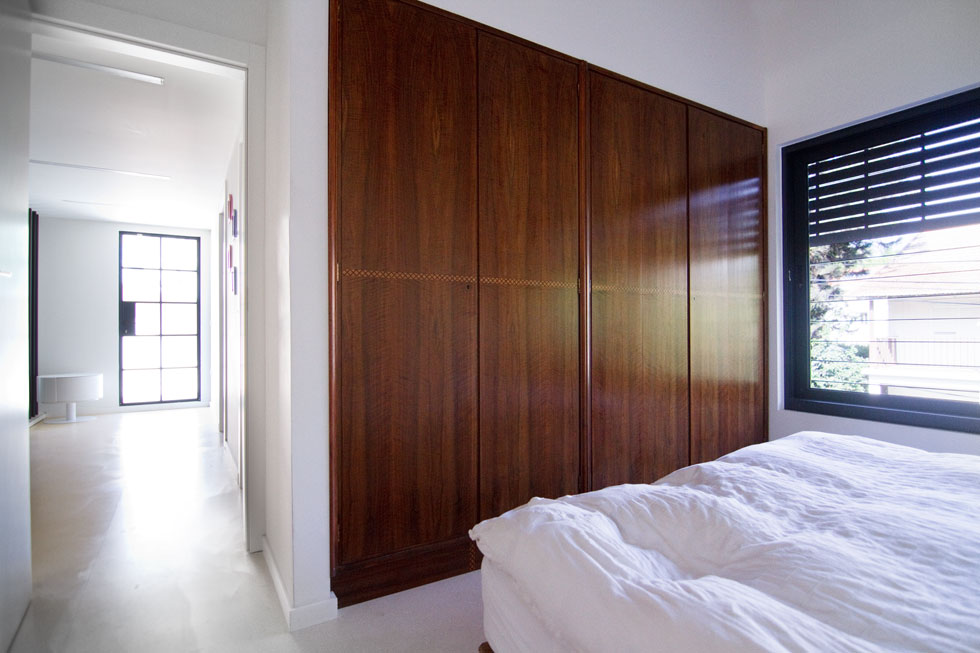 חדרי השינה קומפקטיים, וכוללים רק מיטה וארון קיר שקוע בנישה. בחדר ההורים זהו הארון המקורי, שחודש מבפנים (צילום: אסי אורן)