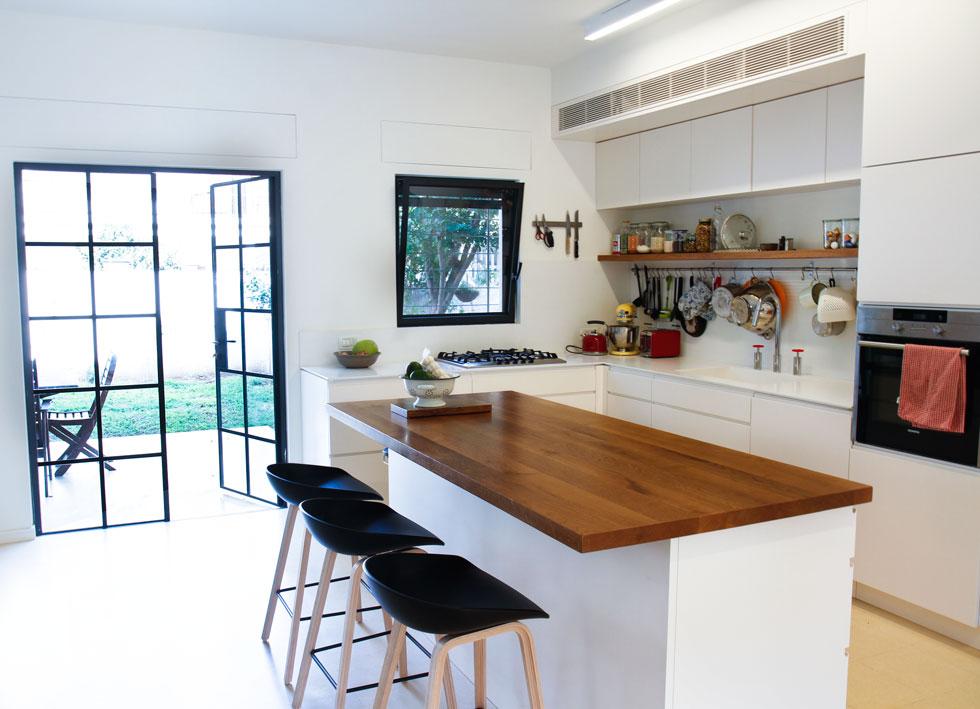המטבח פונה אל החצר. סביב המטבח ושולחן האוכל מתנהלים חיי המשפחה, שכחברים ב''מלאכי שביל ישראל'' גם מרבים לארח (צילום: אסי אורן)