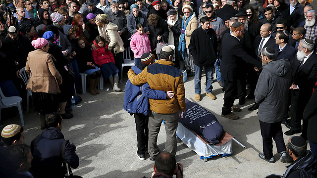 Natan and son Akiva embrace in front of Dafna's body at the funeral (Photo: Reuters)