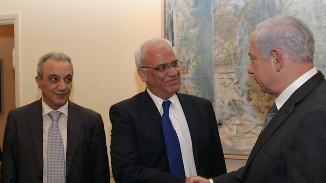 Majid Faraj, left, looking on as Saeb Erekat greets Benjamin Netanyahu (Photo: Amos Ben Gershom)