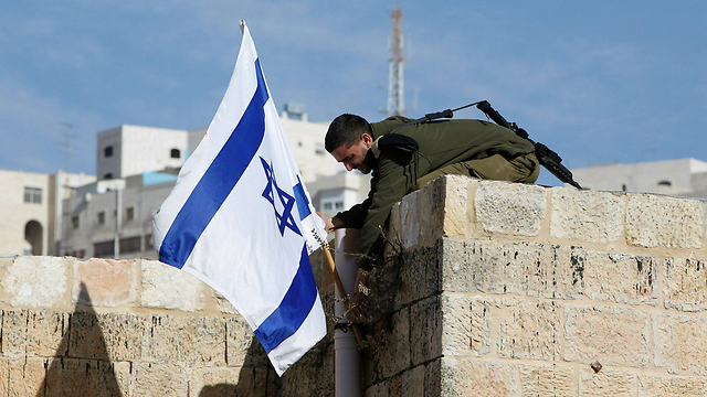 An IDF soldier removing an Israeli flag from a house in Hebron after settlers who had just moved in were evicted (Photo: Reuters)