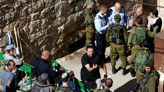 IDF troops evicting the settlers from the two houses in Hebron, the morning after they moved in (Photo: Reuters)