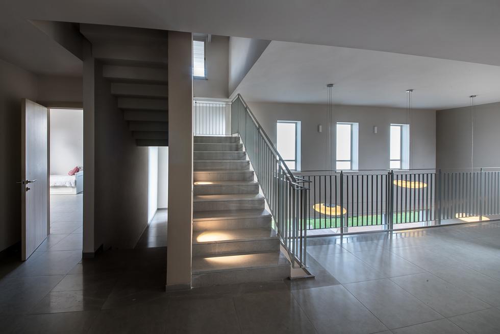 הדיירים אוהבים לראות מי נכנס ומי יוצא מהבית. מבט מהסלון שבקומת חדרי המגורים, הפתוח אל גרם המדרגות והסלון המרכזי (צילום: עמית גושר)