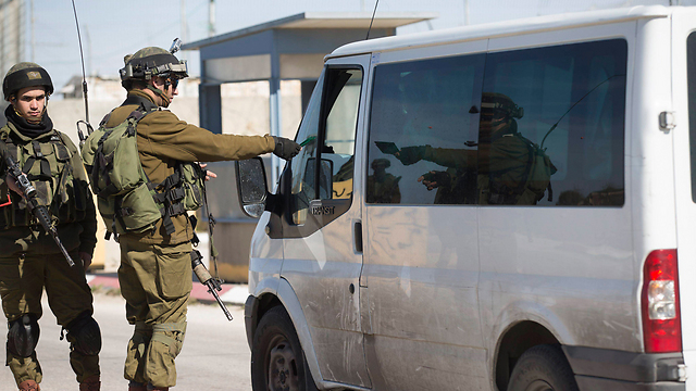 IDF soldiers checking IDs at the entrance to Ramallah (Photo: EPA)