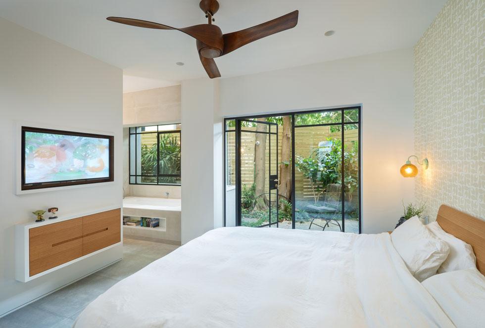 מחדר ההורים יש יציאה לחצר פנימית עם פינת ישיבה קטנה. בפינת הרחצה הצמודה 2 כיורים ואמבטיה שהורכבה בתוך גומחת החלון (צילום: ארקדי רסקין ואלכס פרלמן)
