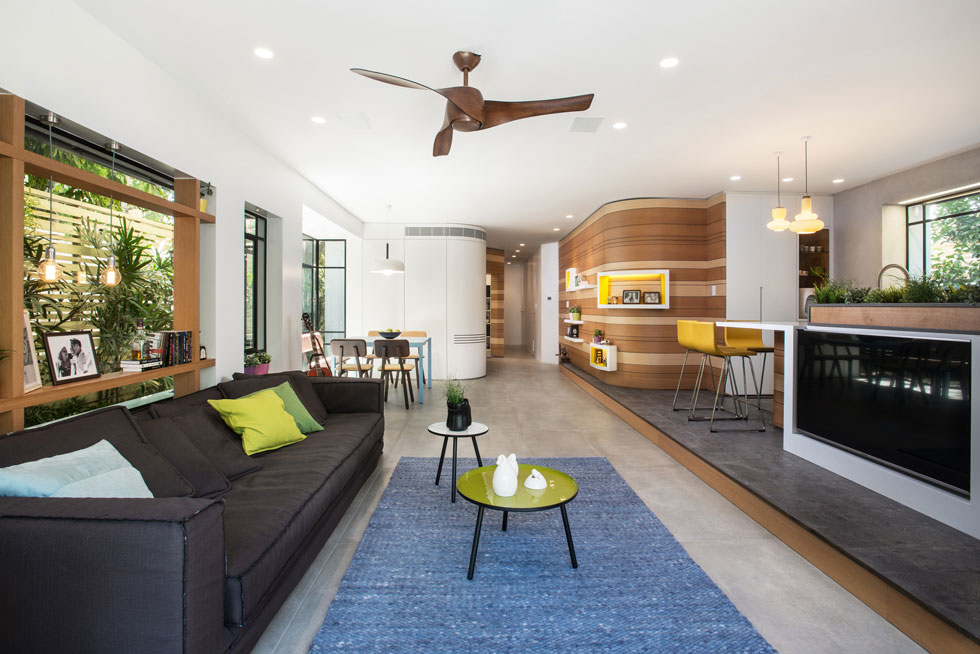 מבט מהסלון לעומק הדירה, אל פינת האוכל והמסדרון המוביל לחדרים הפרטיים. מאחורי הספה, בנישת החלון, נבנתה ספרייה קלילה המשמשת לה כגב (צילום: ארקדי רסקין ואלכס פרלמן)