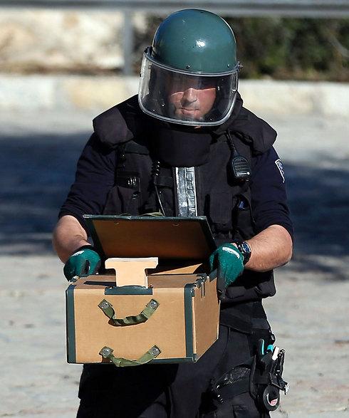 חבלן משטרתי עם חפץ שנחשד כמטען חבלה (צילום: AFP) (צילום: AFP)