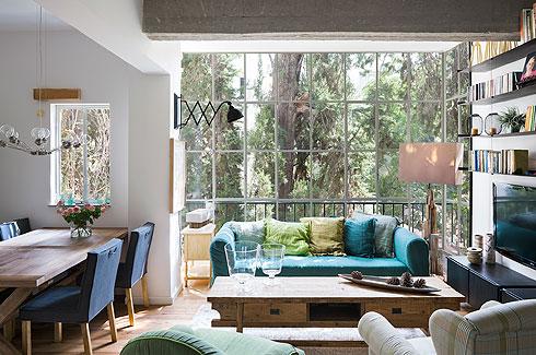 רקע לפינת הישיבה נותנים החלון שחולק לריבועים שווים וספריית המתכת שנבנתה לגובה הקיר (צילום: שי אפשטיין)