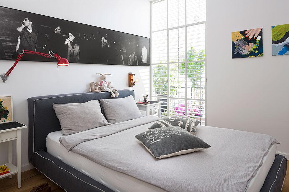 בחדר השינה נתלה צילום של יאיר ברק, שהיה בבית הקודם ובעלת הבית ביקשה למצוא לו מקום ראוי. המרפסת בצד הושארה, אך דלת היציאה הוחלפה בחלון קבוע (צילום: שי אפשטיין)