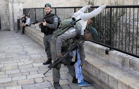 Border Police frisking Arab man at the Damascus Gate.