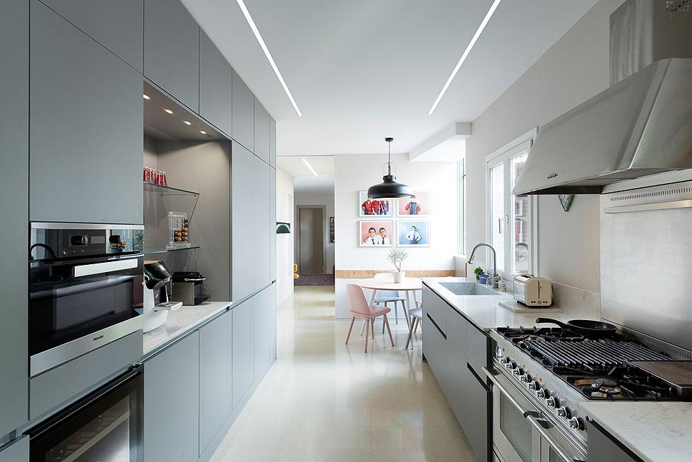 המטבח תוכנן במחשבה מעשית מאוד. בקצהו פינת אוכל לארוחות יומיומיות, ואחריה חדר המשפחה. כדי ליצור הפרדה מלאה בין האגפים, דלת הזזה רחבה שנבלעת בתוך הקיר מפרידה בין המטבח לחדר המשפחה. ''זה פתרון גאוני'', אומר האב, ''כשיש אורחים אנחנו סוגרים – להם יש פרטיות ולנו יש פרטיות'' (צילום: גדעון לוין)