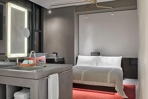 חדר בבניין הדואר. הצבעים השולטים הם אפור, שחור ואדום, והמנורה מצינורות פליז (צילום: Lutz Vorderwuelbecke באדיבות: W interiors-courtesy of W Amsterdam)