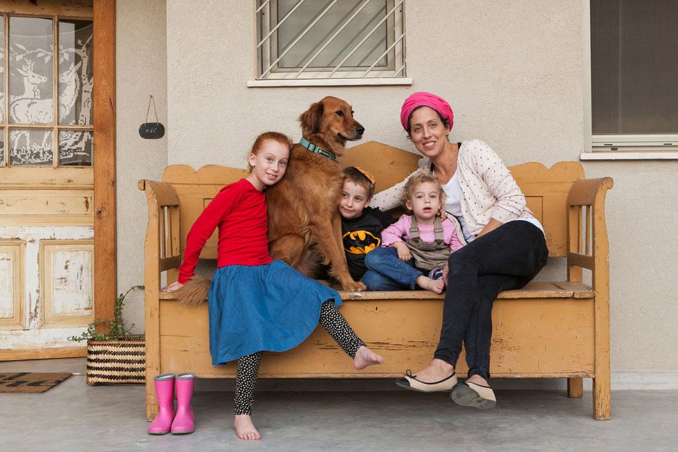 מירב גליס-המלי, מעצבת גרפית שפתחה קריירה שנייה בעיצוב פנים, עם שלושת הילדים והכלב ברחבת הכניסה. השינוי בסגנון החיים בהתנחלויות החדשות ניכר: בבתים הנאים והמעוצבים, בבגדים המעודכנים ובקריירות המטופחות. גליס-המליס מספרת שבין 130 המשפחות ביישוב יש חמש אדריכליות צעירות (צילום: שירן כרמל)