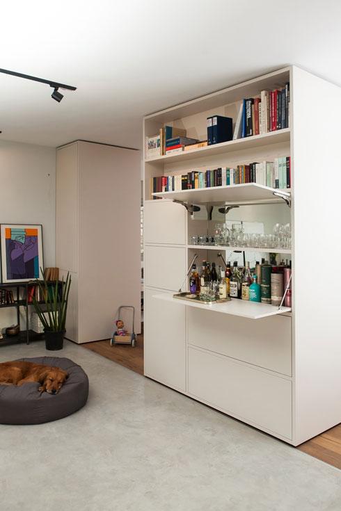 הארון שיוצר הפרדה חלקית בין הסלון לחדר המשפחה, ומסמן את המעבר מרצפת הבטון לפרקט האלון (צילום: שירן כרמל)