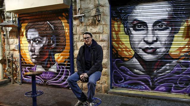 Solomon Souza with two of his shutter-portraits at Mahane Yehuda market (Photo: Reuters)