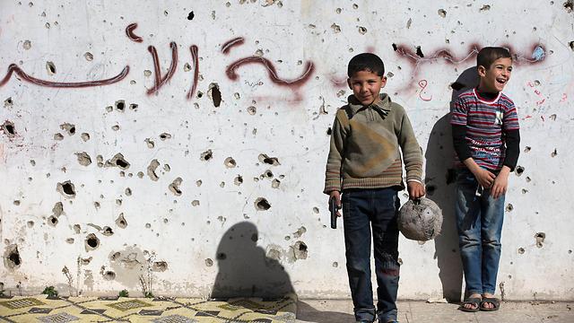 מנסים לשמור על חיוך. ילדים משחקים בחומס (צילום: AP) (צילום: AP)