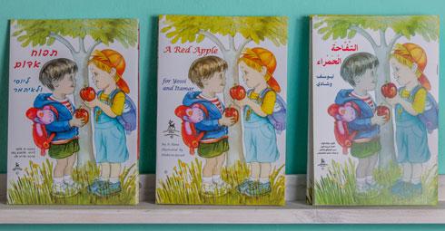 """הספר """"תפוח אדום ליוסי ולאיתמר"""" במהדורה העברית (משמאל), האנגלית והערבית (צילום: ירדן מרקוס)"""