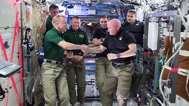 """קלי (מימין) בטקס החלפת הפיקוד בתחנת החלל הבינלאומית (צילום: נאס""""א) (צילום: נאס"""