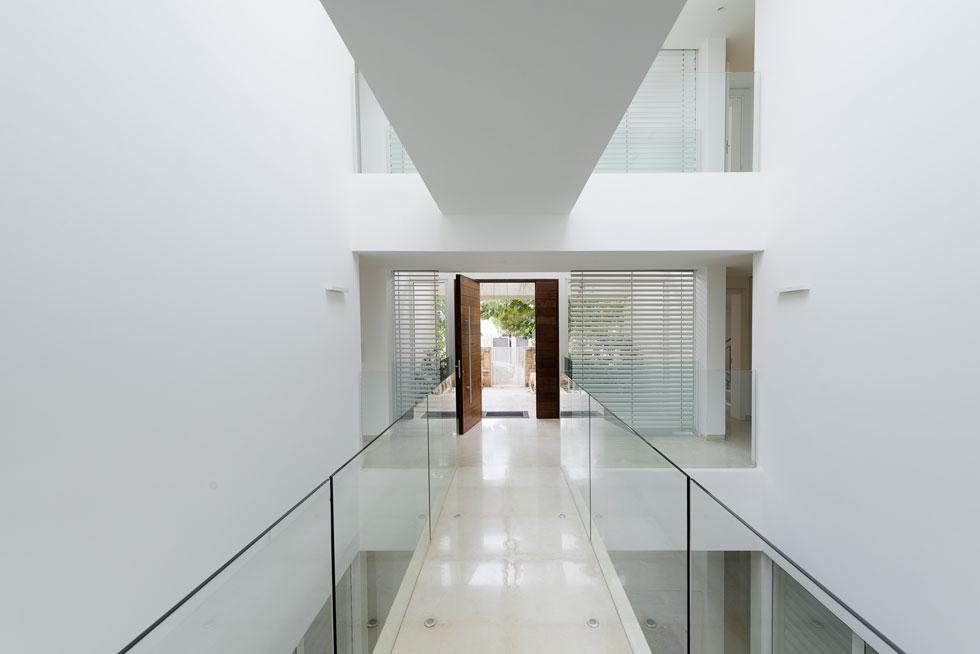 שטח הבית 350 מטרים רבועים, שחולקו לתשע קוביות שוות בגודלן. בכניסה תוכנן חלל שמתנשא לגובה שלוש הקומות ומסתיים בחלון סקיי-לייט. כך מתאפשר מבט אל כל חלקי הבית ואור טבעי נכנס גם לקומת המרתף (צילום: גדעון לוין)