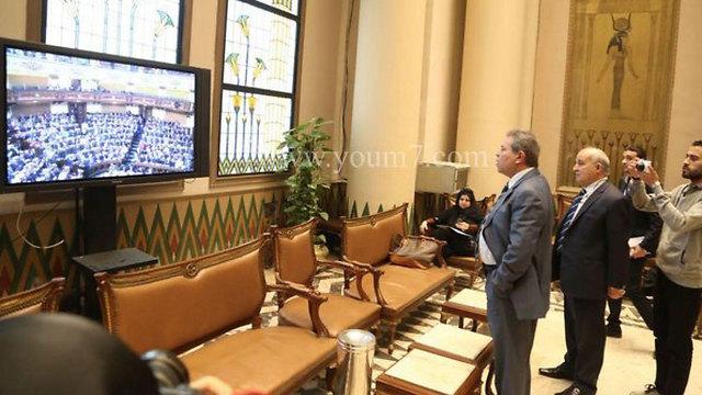 עוכאשה צופה בדיון, מחוץ לאולם הפרלמנט ()