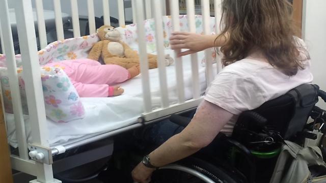 גם ההורים בכסאות גלגלים יכולים להוציא את התינוק מהמיטה ()