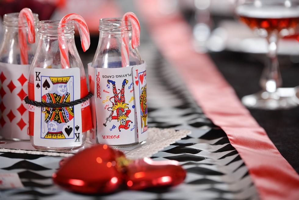 להשלמת מראה השולחן, מקשטים בקבוקי זכוכית בקלפים ומוסיפים קשיות בצבע אדום-לבן, ומפזרים לבבות אדומים (צילום: מיה לוי)