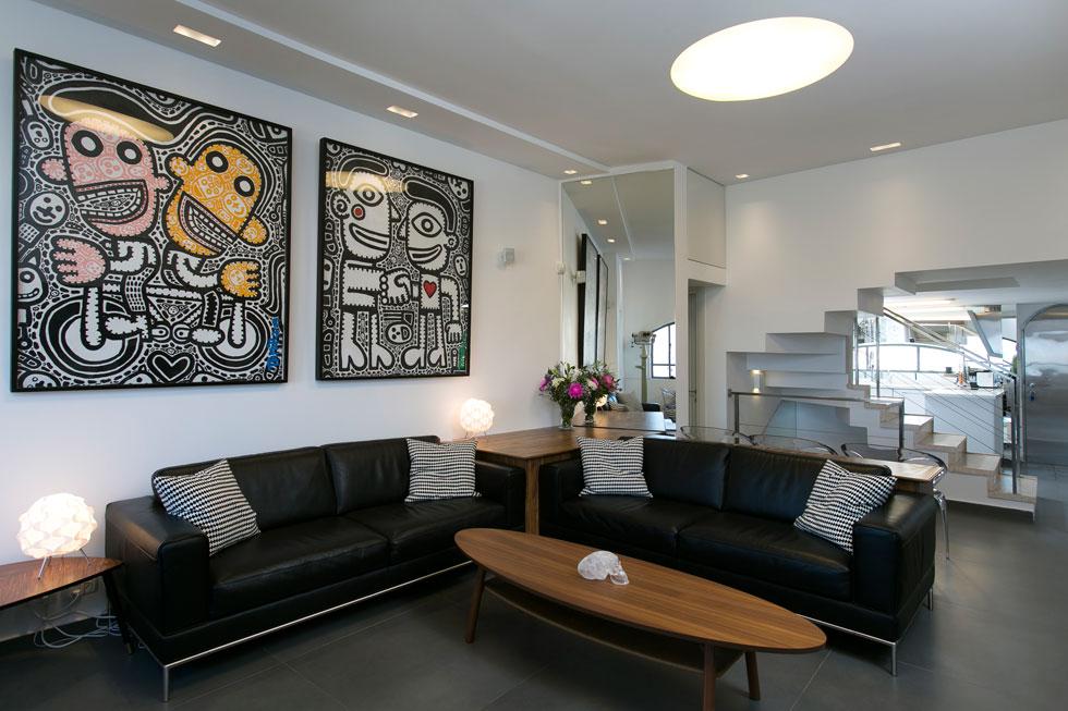 בסלון רהיטים מ''איקאה'' ועל הקיר שני ציורים עצומים של תמיר שפר. ''אני אוהב סגנון נקי ומינימליסטי'', אומר גלר. ''ירדתי מקישוטים''. אבל הציורים של שפר כבשו אותו: ''הוא מראה את הכאוס סביב האנושות בעולם, ובתוכו מראה לחיצת ידיים, שאיפה לשלום ולאהבה'' (צילום: שירן כרמל)